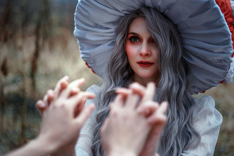 Portrait of woman holding hands