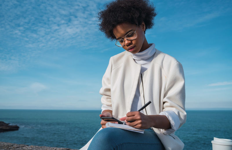 Woman writing in diary while sitting against sky