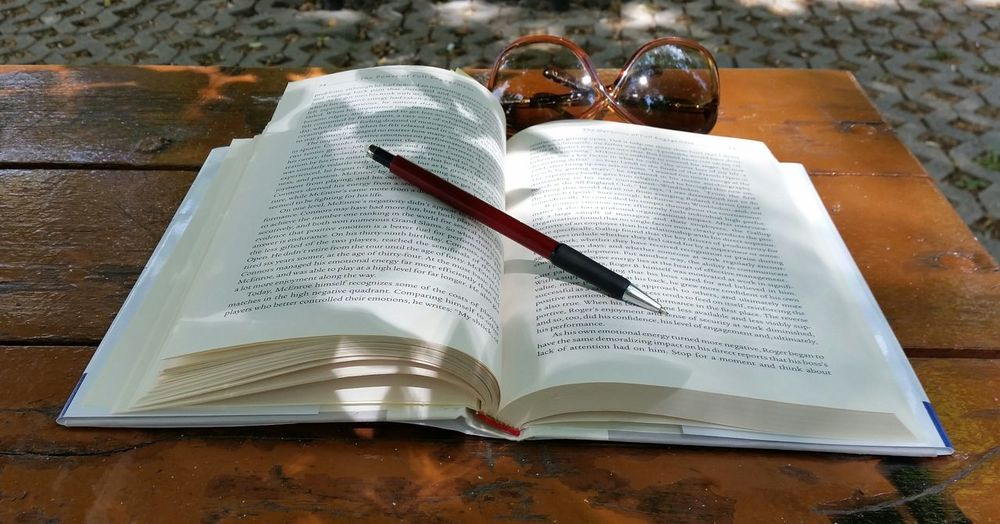High angle view of book and pen by sunglasses on table