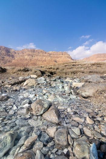 Rocks on land against blue sky