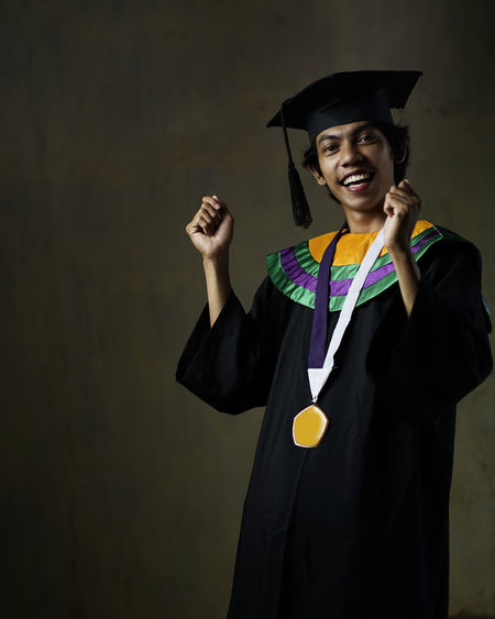 Portrait of smiling man wearing graduation gown standing against wall