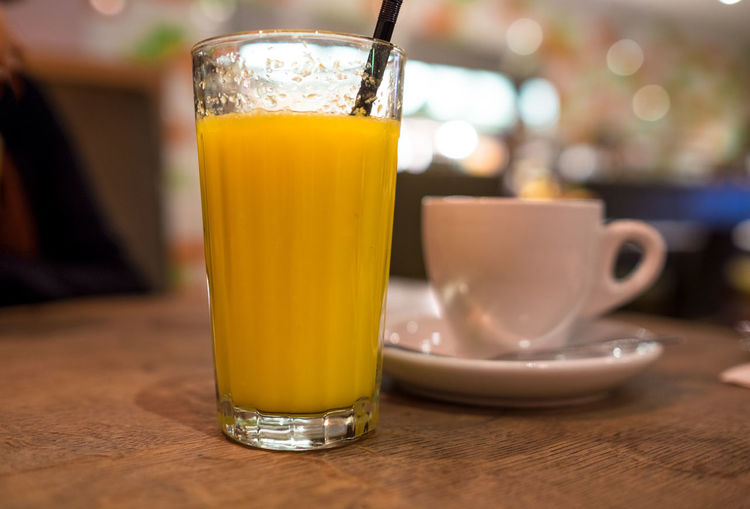 Close-up of orange juice glass with coffee cup on table