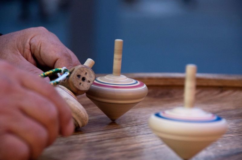 Cropped Hand By Wooden Spinning Top On Table