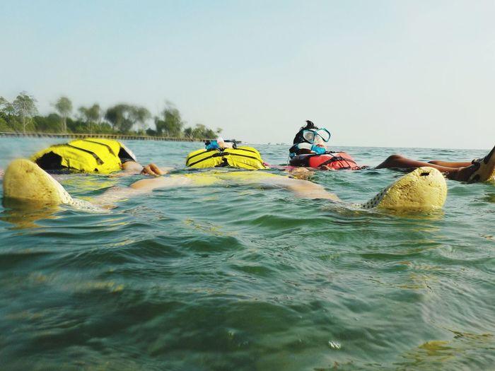 Friends Snorkeling In Sea Against Clear Sky