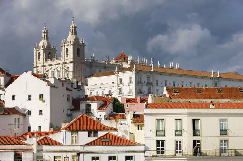 Monastery Of Sao Vicente De Fora By Buildings Against Cloudy Sky