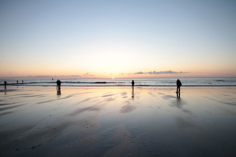 Silhouette person standing on beach against clear sky during sunset