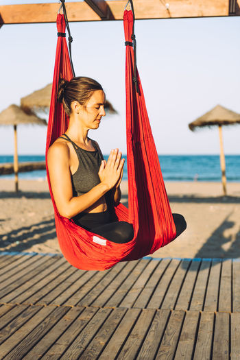 Woman meditating while sitting on silk at beach
