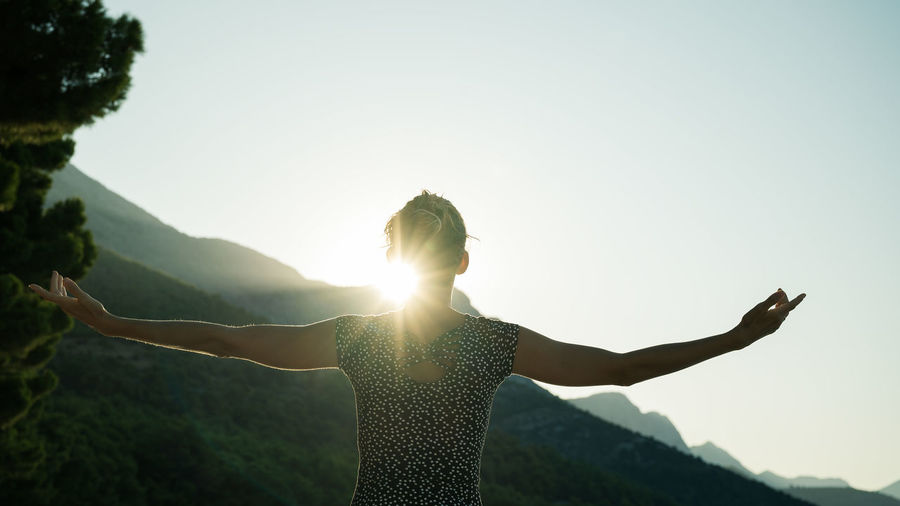 Woman standing with arms outstretched against clear sky
