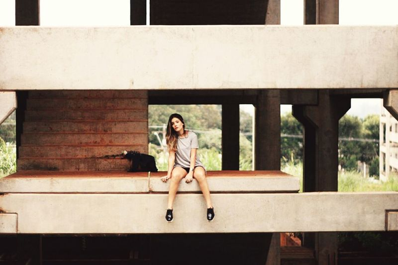 Portrait Of Woman Sitting At Incomplete Building