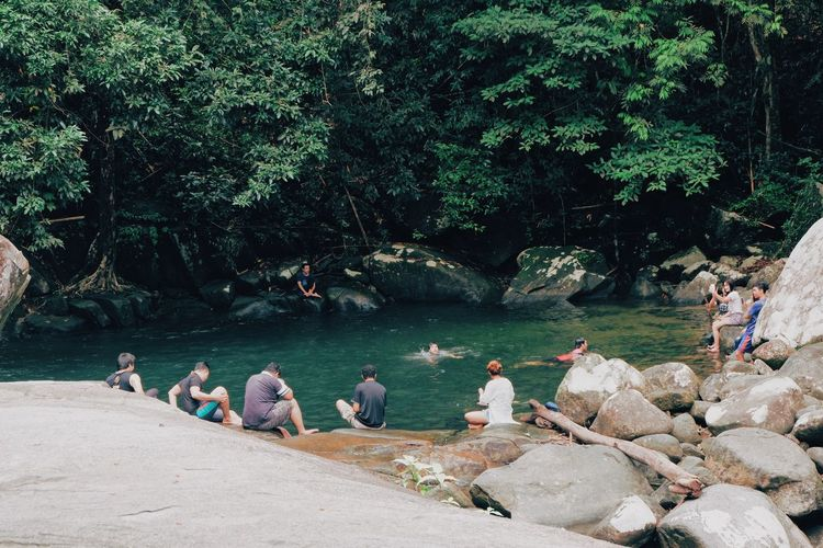 Group of people sitting on rocks by trees