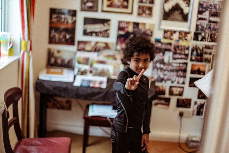 Cheeky boy taking singing lessons waiving finger.. Boy Waving Pointing Interior Candid Afro Cute Mixed Race Mixed Sweet Photography Photooftheday Books Bookshelf Sheet Music Singing Singing Lesson Lesson Teachers Urban Lifestyle Light Light And Shadow