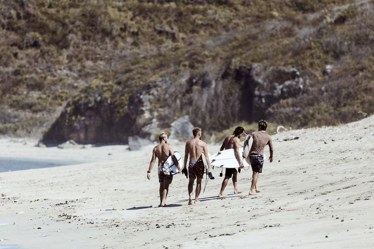 Rear view of people walking on beach