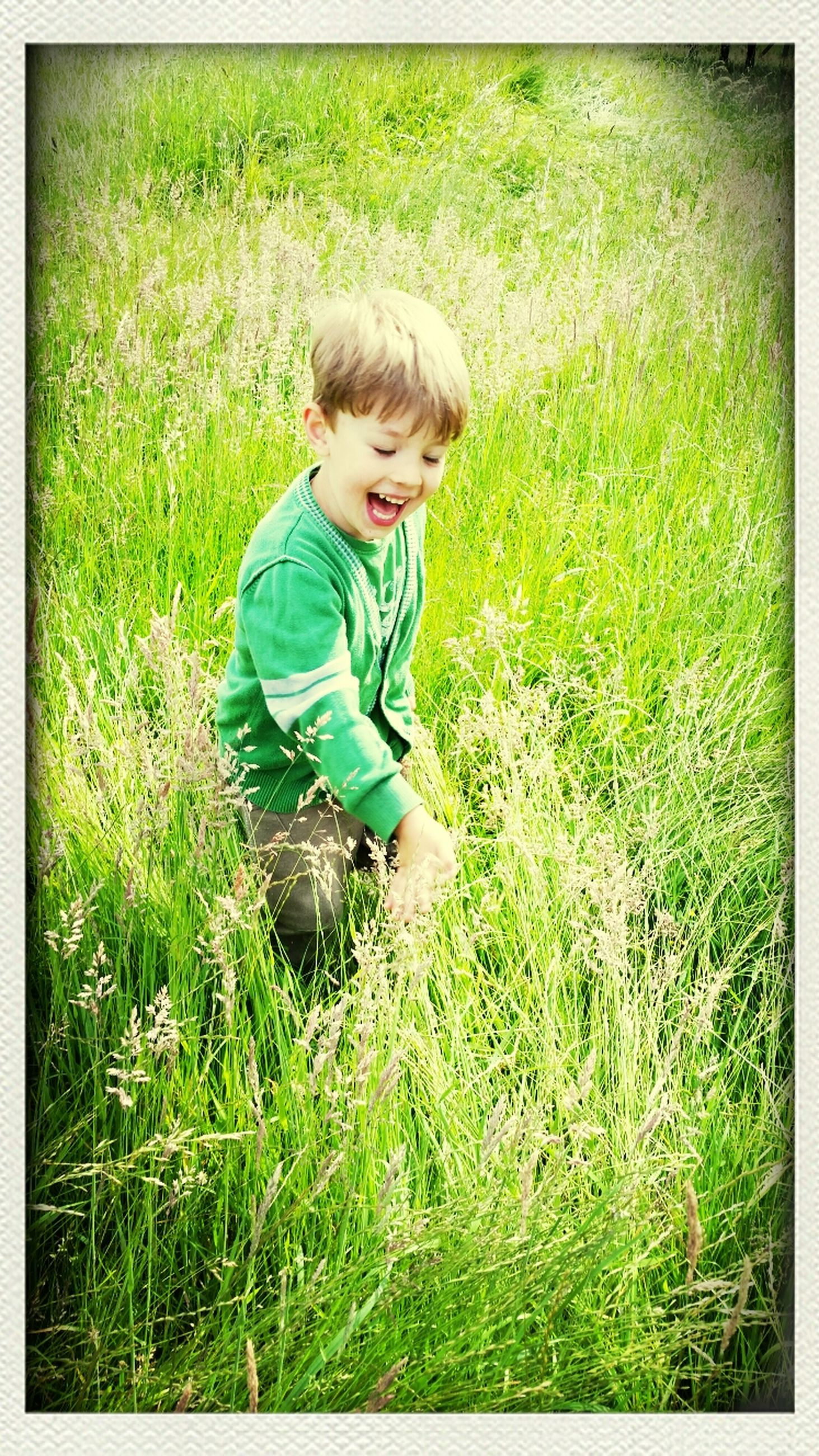 transfer print, grass, auto post production filter, full length, field, grassy, person, childhood, green color, elementary age, lifestyles, casual clothing, leisure activity, one animal, looking at camera, portrait, sitting, plant