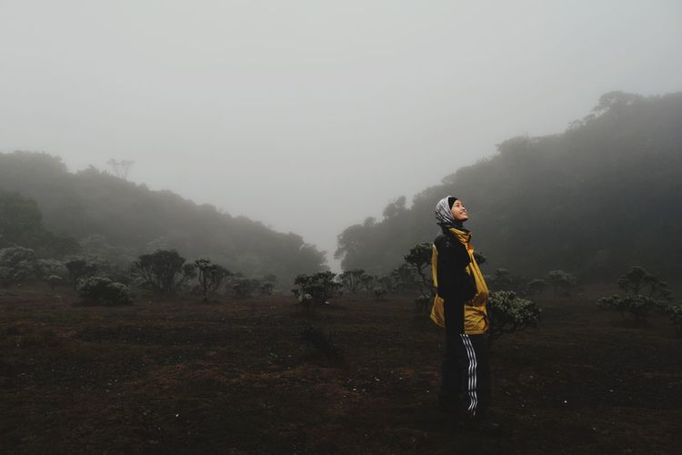 Woman standing on land during foggy weather
