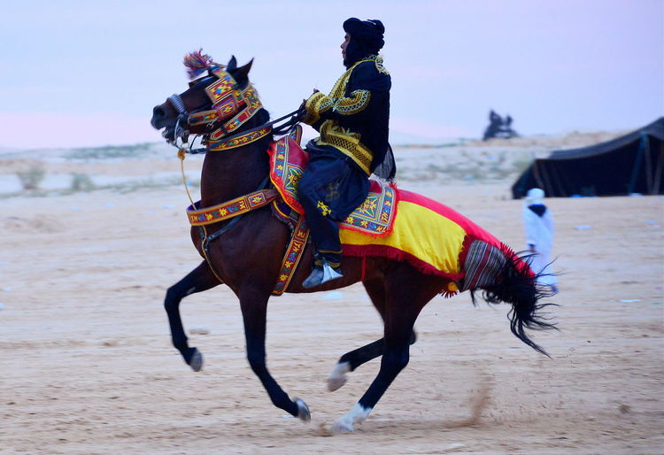 Man in traditional clothing riding horse on sand
