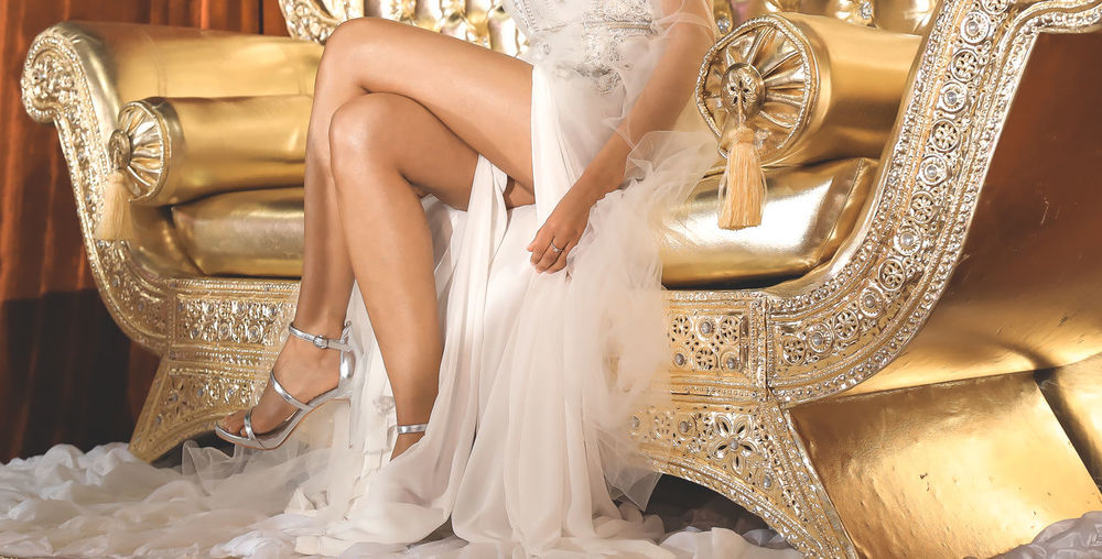 Low section of woman in wedding dress on golden chair