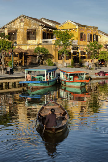 Boats moored in canal by buildings in city