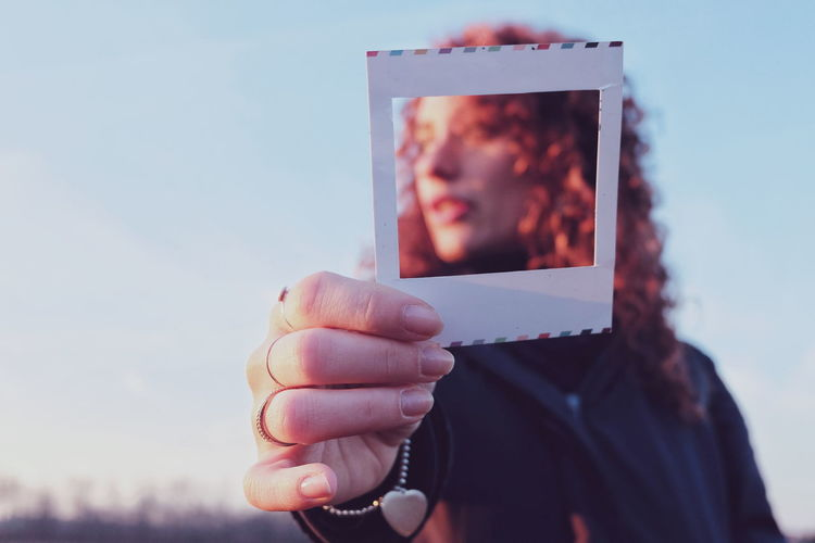 Portrait of woman holding frame against sky
