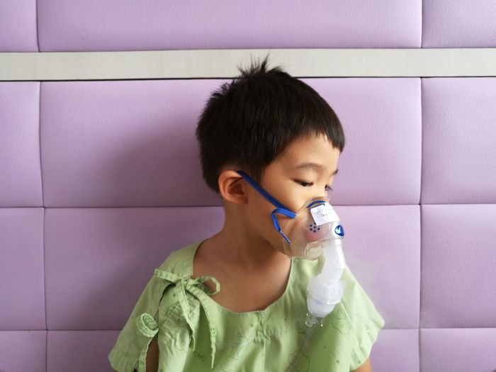 Close-Up Of Cute Boy Wearing Oxygen Mask