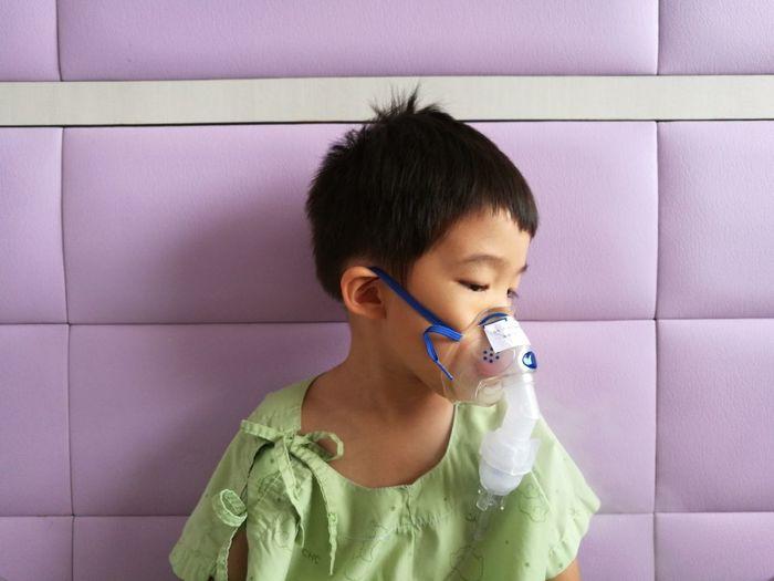 Close-up of cute boy wearing oxygen mask