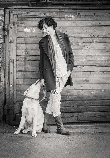 Full length of woman with dog on wooden floor