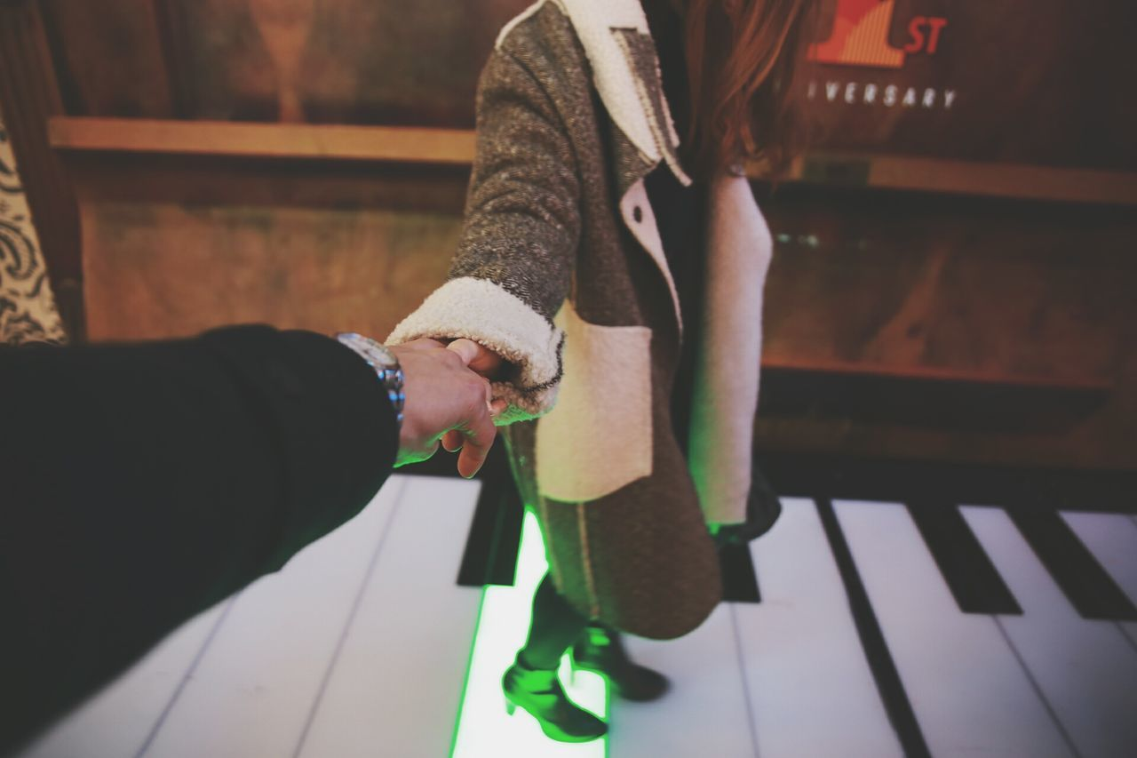 Couple holding hands on piano flooring