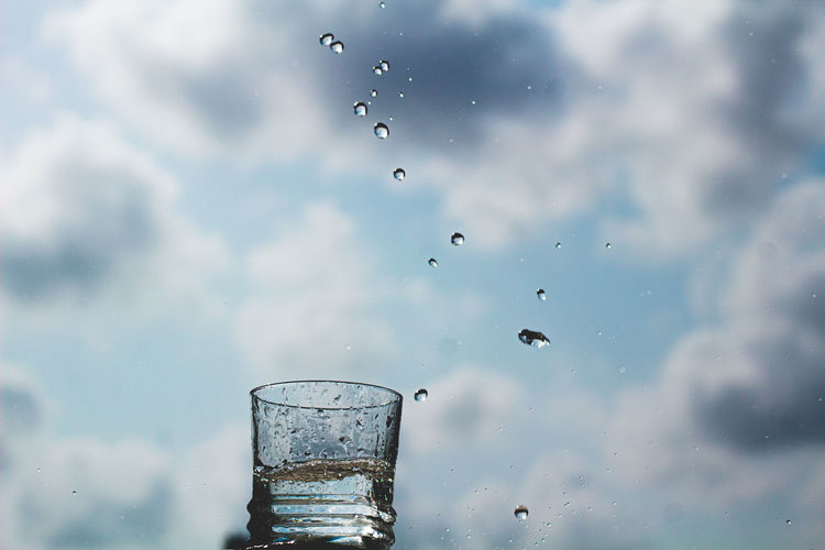 Low angle view of glass of water against sky