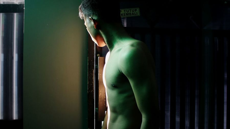 Side view of shirtless man standing by window