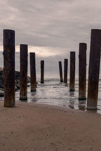 Wooden posts on beach against sky during sunset