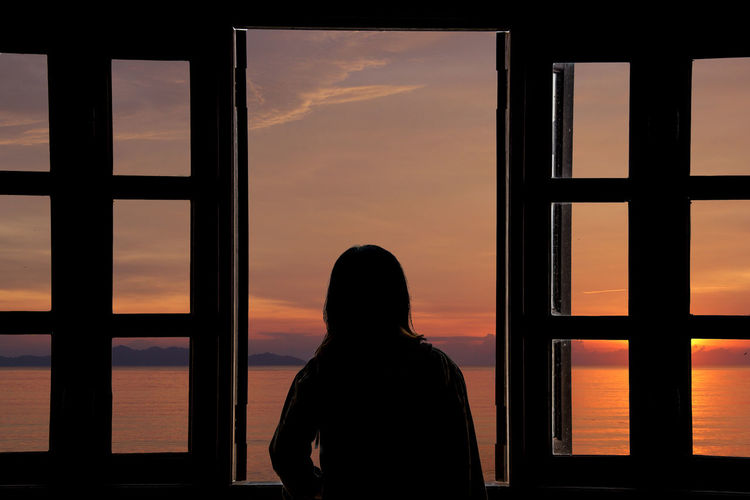 Rear view of silhouette woman looking at sunset seen through window