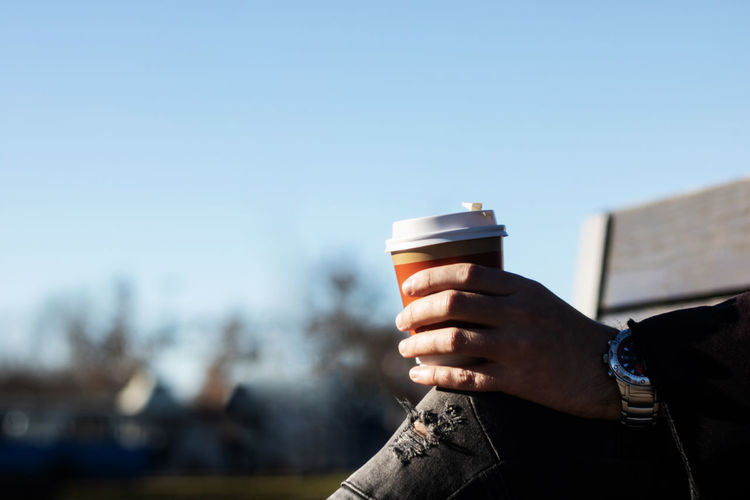 Man holding coffee cup against clear sky