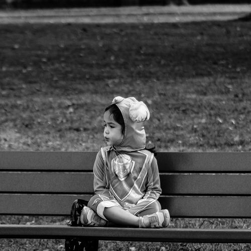 Girl wearing costume while sitting on bench at park