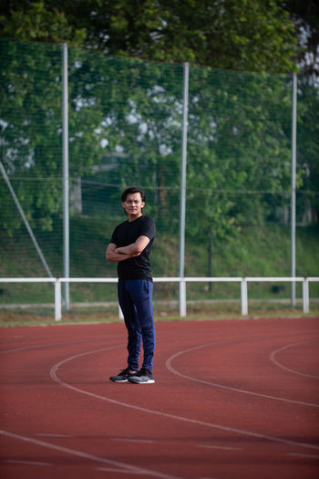 Malaysian Male Athlete Working out at a stadium Sport Full Length Sport Training Athlete Healthy Lifestyle Track And Field Conceptual Malaysia Asian  Malay Stadium One Person Real People Lifestyles Running Track Day Front View Man Males