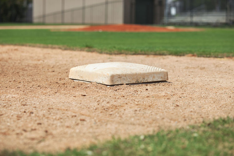 Low angle view of third base on a baseball infield Baseball Field Dirt Grass Green Color Sport Sunlight Youth Outdoors No People Photography Infield Low Angle View Selective Focus Bleachers Gravel