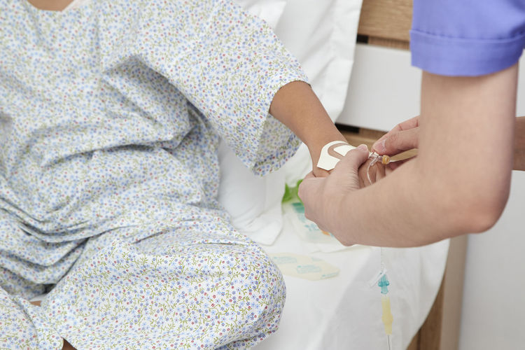Midsection Of Nurse Holding Patient Hand