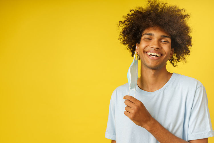 Portrait of a smiling young man against yellow background