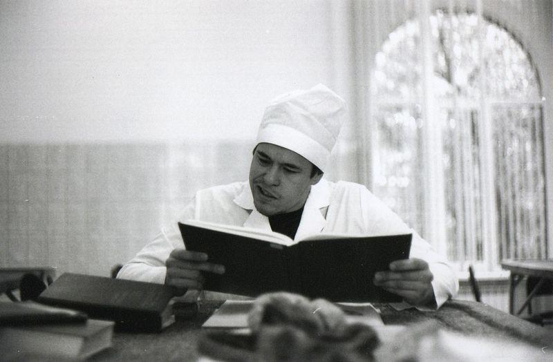 Man reading book at table