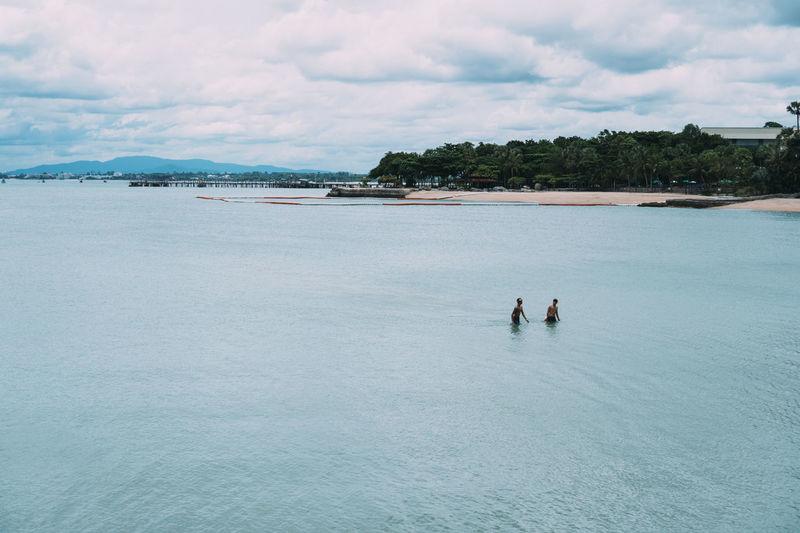 Men in sea against cloudy sky