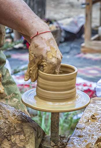 Cropped hands of potter working outdoors