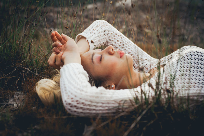 Close-Up Of Young Woman Resting On Grass