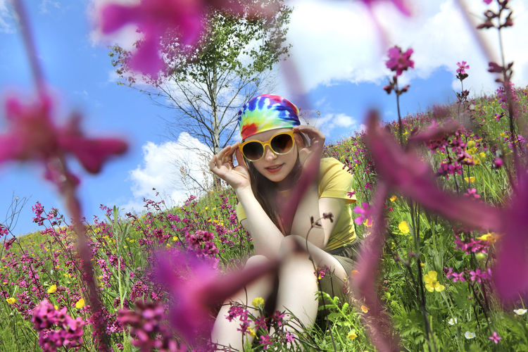 Portrait of smiling woman with pink flowers against trees