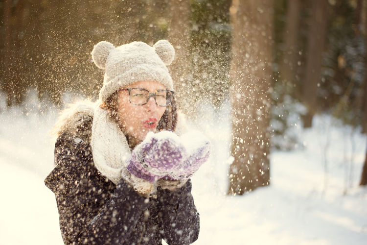 Adult Adults Only Blowing Cheerful Cold Temperature Day Enjoyment Fun Happiness Human Body Part Leisure Activity Mature Adult Motion One Person One Woman Only Only Women Outdoors People Smiling Snow Snowflake Snowing Warm Clothing Winter Women