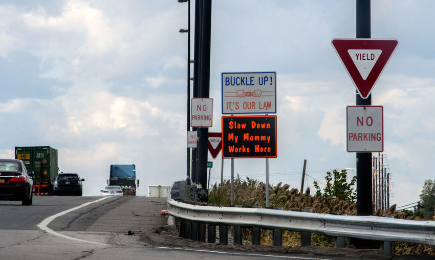 unique signs dot the on ramp of a highway in Ohio USA Sign Communication Transportation Text Road Motor Vehicle Cloud - Sky Land Vehicle Sky Mode Of Transportation Truck Road Sign Day Western Script Nature Car No People Guidance Semi-truck Outdoors On Ramp Ohio USA Travel Destinations Warning Signs