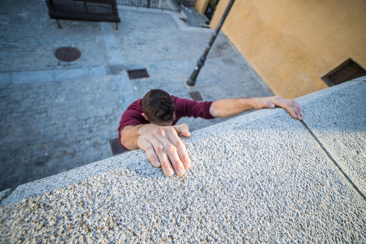 High Angle View Of Man Climbing Concrete Wall