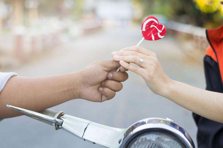 Close-Up Of Hands Holding Red Lollipop