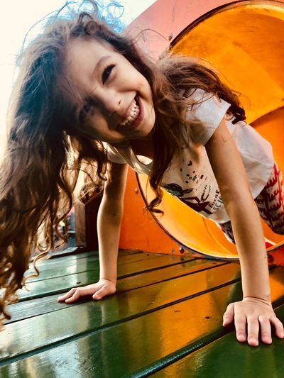 Portrait Of Happy Girl Playing On Slide