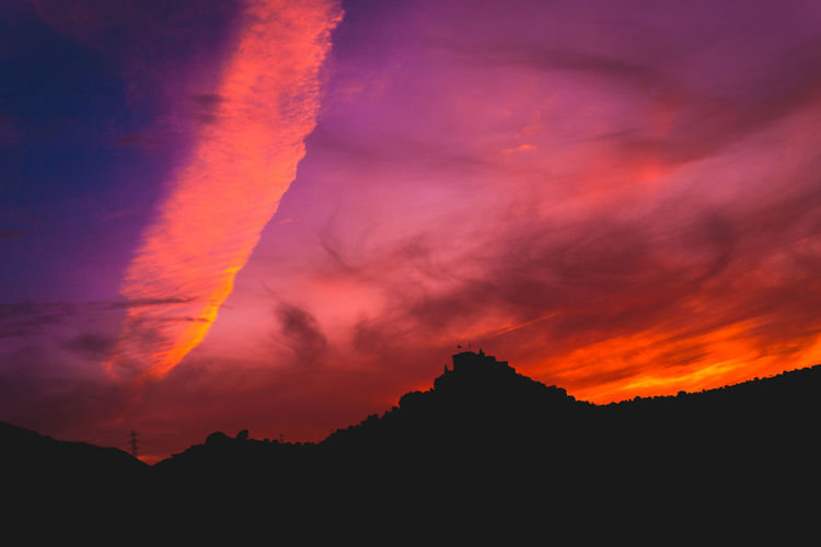 Scenic view of silhouette mountain against dramatic sky during sunset