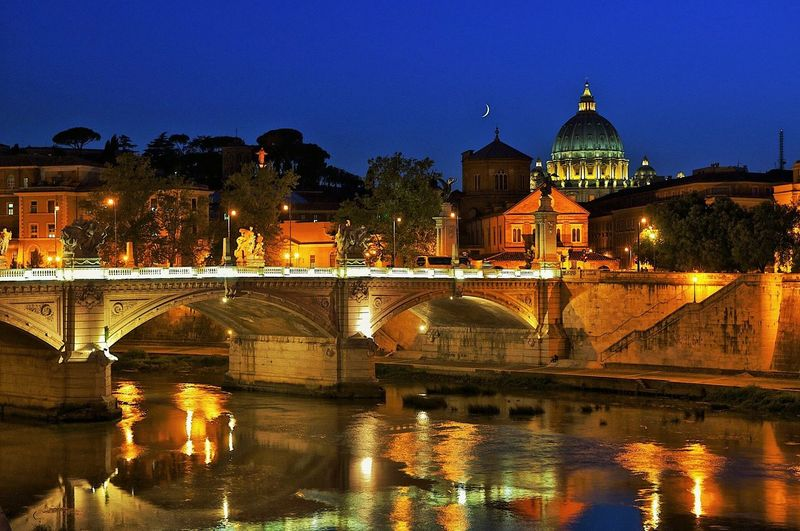 Illuminated bridge over tiber river against blue sky