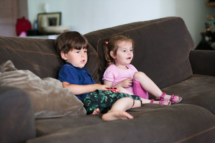 Siblings playing video game while sitting on sofa at home