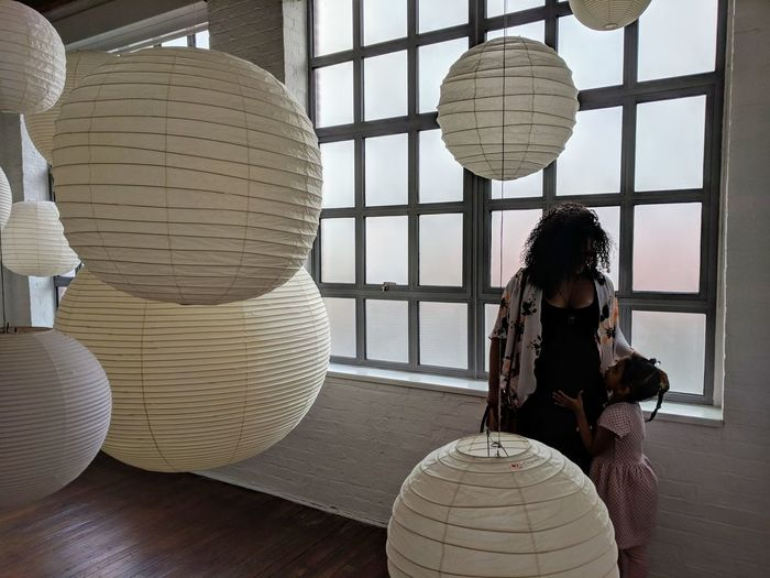 Mother And Daughter Standing By Paper Lanterns Hanging Against Window